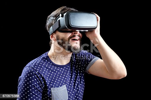 istock Man in blue dotted T-shirt wearing virtual reality 3d-headset isolated on black 670975388