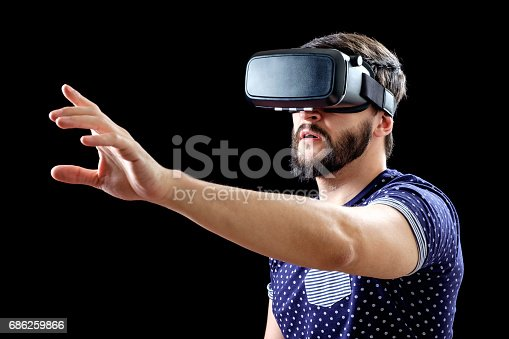 istock Man in blue dotted T-shirt wearing virtual reality 3d-headset isolated on black 686259866