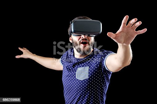 istock Man in blue dotted T-shirt wearing virtual reality 3d-headset isolated on black 686259868