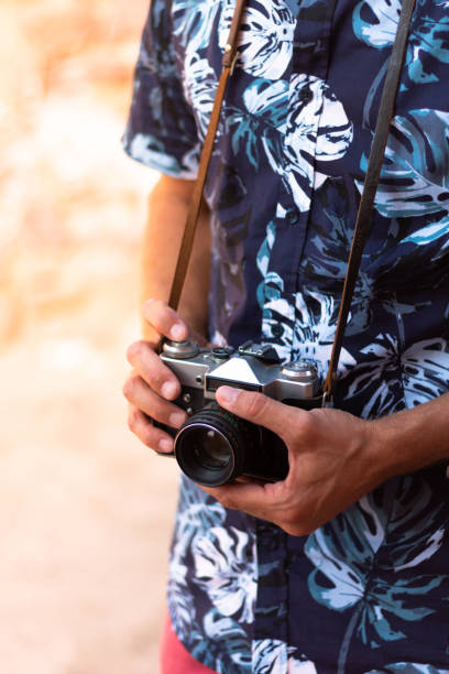 Man in blue hawaiian shirt and an old camera hanged on his neck ready to shoot stock photo