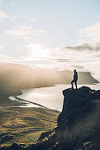 Young Caucasian man in blue raincoat  looking at scenic view of fjord in Westfjorden in Iceland
