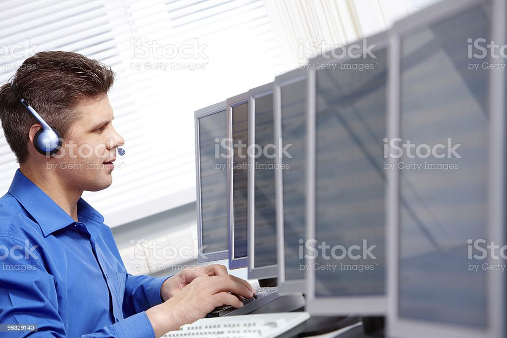 Man in blue shirt and headset typing in a computer room royalty-free stock photo