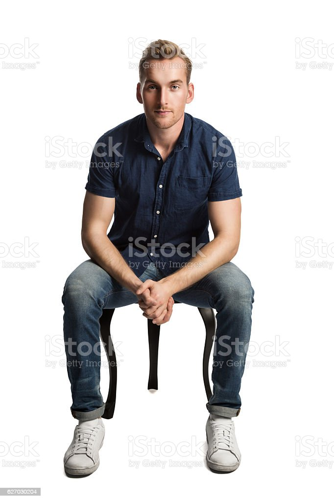 Man in blue shirt and jeans sitting down stock photo