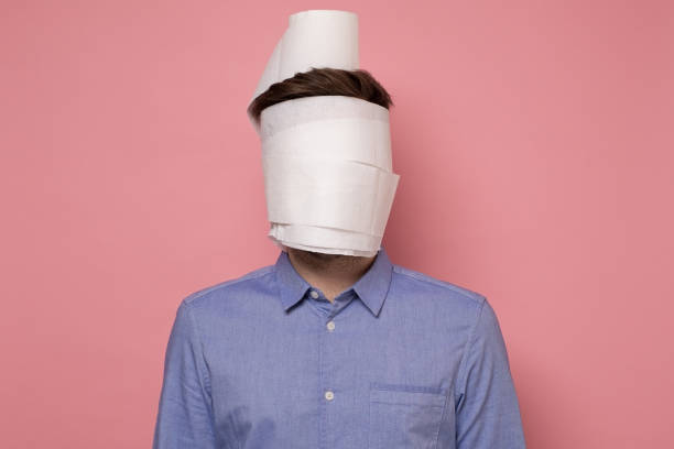 Man in blue shirt wrapped his face in a paper trying to protect himself from coronavirus. stock photo
