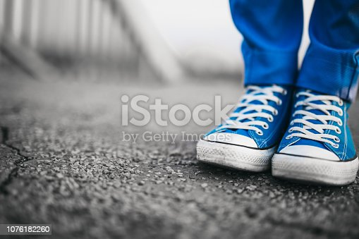Close-up of man's legs in blue sneakers