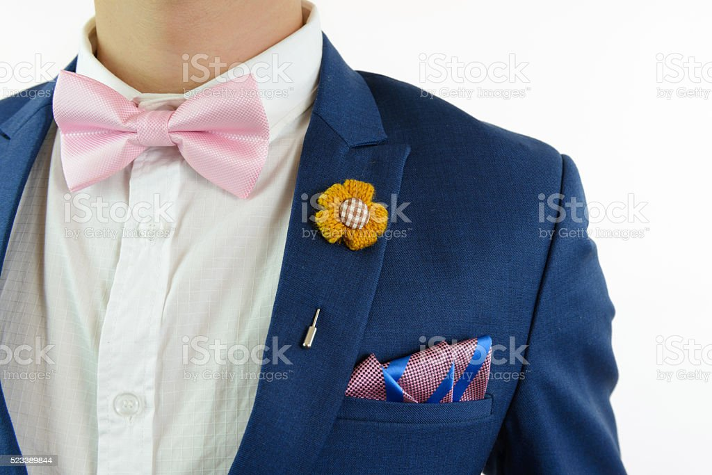 Man in blue suit with pink bow tie, flower brooch, and pink blue...