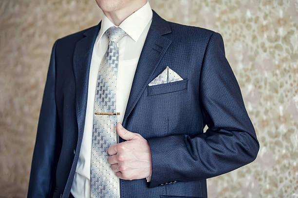 mann im blauen anzug mit krawatte, fliege clip und taschentuch - krawattennadel stock-fotos und bilder