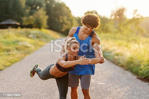 511849865istockphoto Man in blue t-shirt helping blonde woman with ponytail to do balance exercise in nature. Summer day. Three quarter length. 1126913903