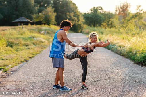 511849865istockphoto Man in blue t-shirt helping blonde woman with ponytail to do balance exercise in nature. Summer day. Full length. 1126914771