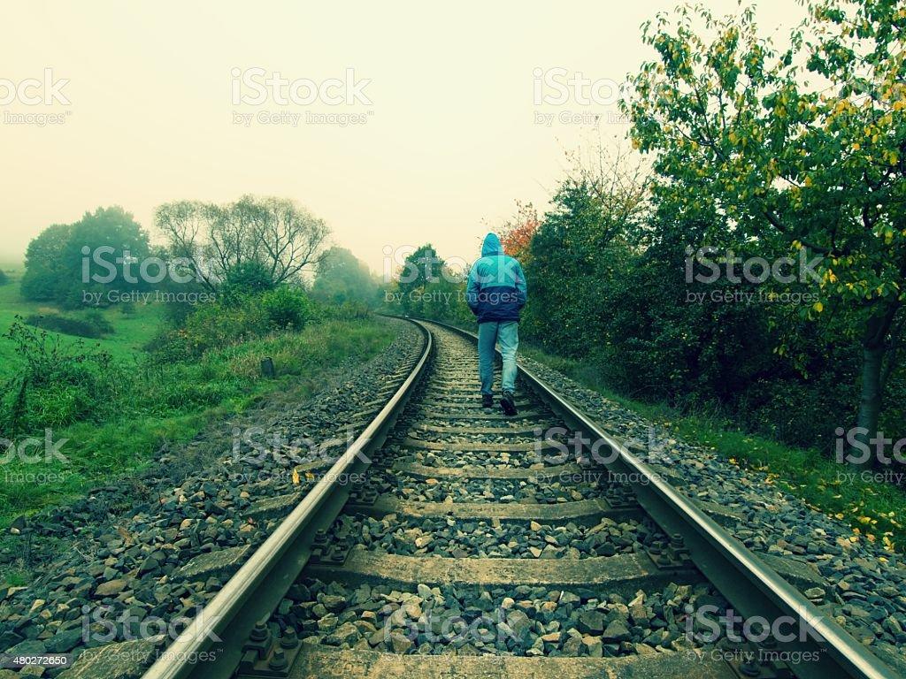Man in blue windcheater walks on railway stock photo