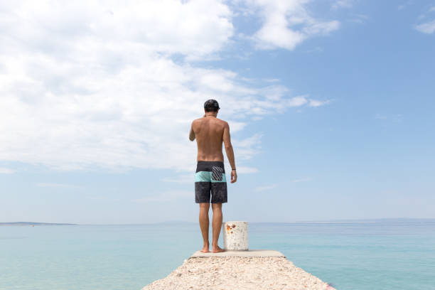 Man in board shorts standing at the end of the pier in summer stock photo