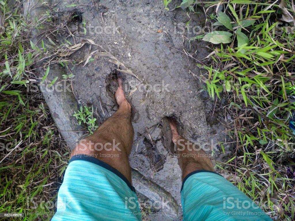 Man in boardshorts walking in mud stock photo