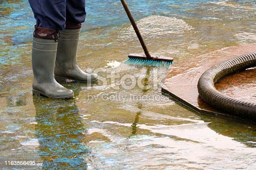 man in boots cleans after the summer season the bottom of the fountain, brush and pump