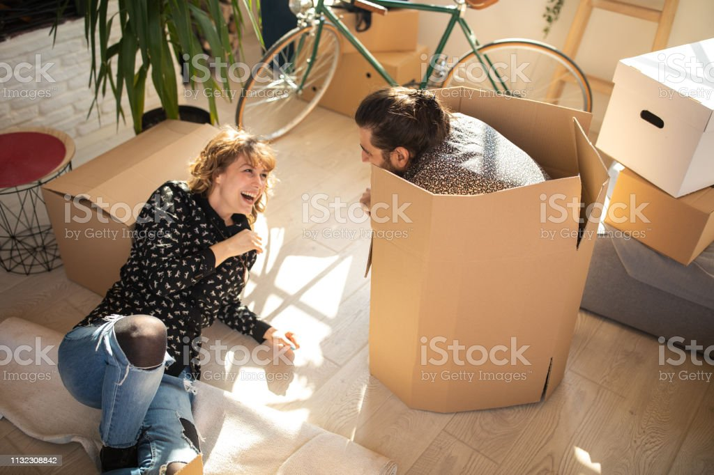 High angle view of young funny couple, man crouching in cardboard...