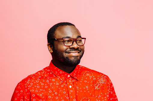 Man in bright red shirt and glasses  smiling and looking off camera