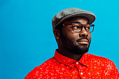 istock Man in bright red shirt, glasses and cap looking off camera 1139114190