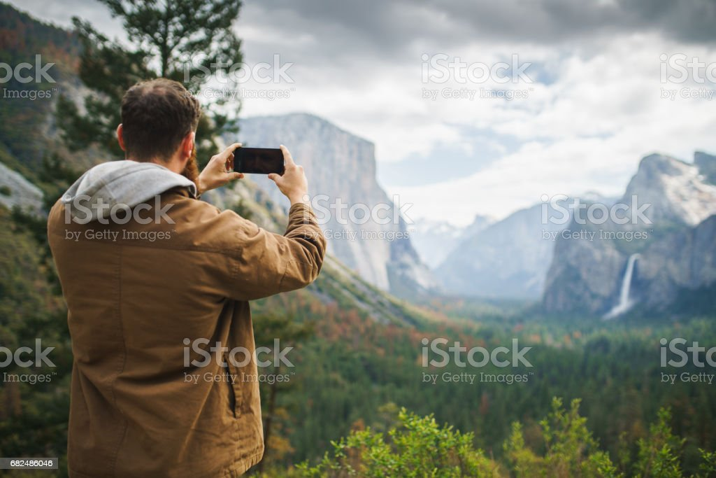 man in brown coat taking photo of yosemite royalty-free stock photo