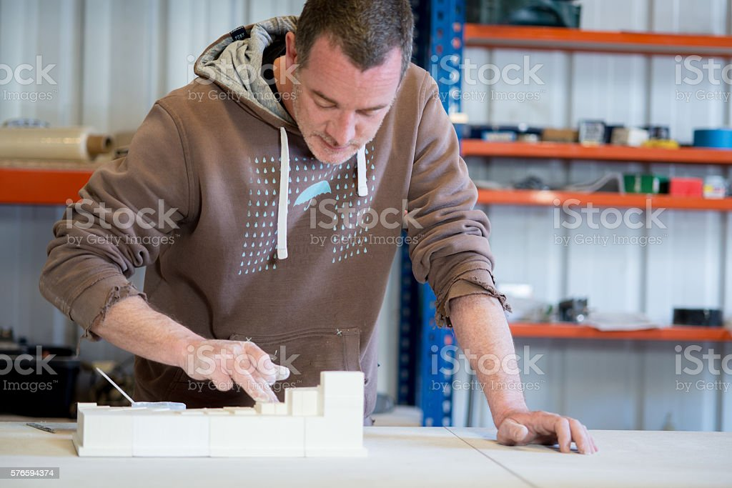 Man in Brown Hoodie Smearing White Paint on Plaster Model A caucasian man in brown hoodie smearing white paint on plaster model building on table. Adult Stock Photo