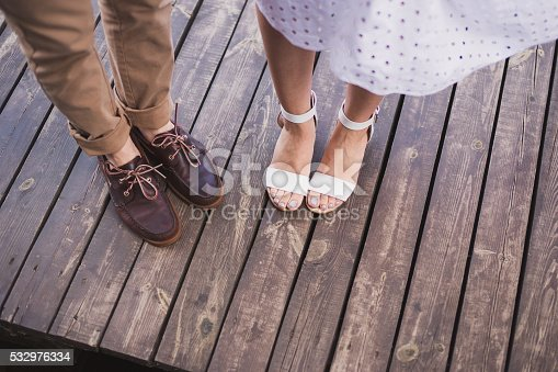 man in brown leather shoes and woman in white open footwear stand side by side on wooden surface