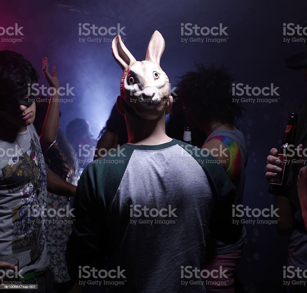 Man in bunny mask dancing in night club royalty free stockfoto