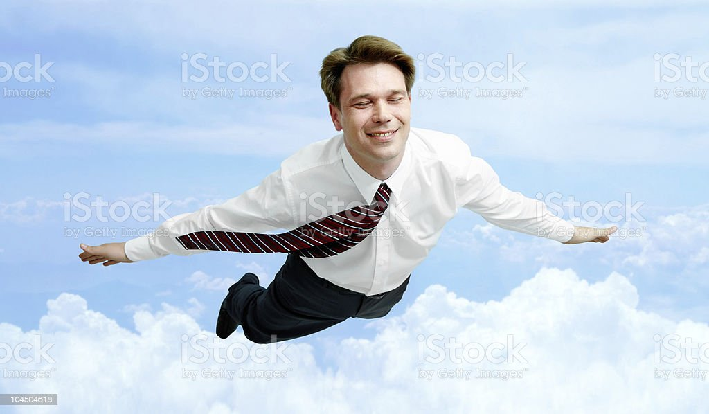 Man in business clothes soaring above the clouds royalty-free stock photo