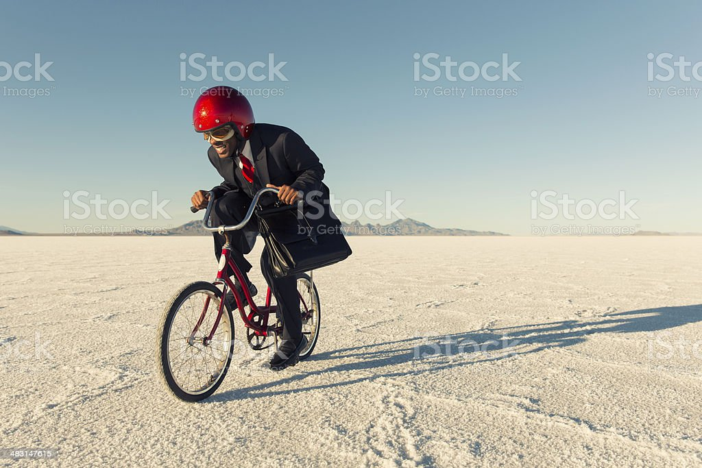 Man in Business Suit and Racing Helmet Races his Bicycle stock photo