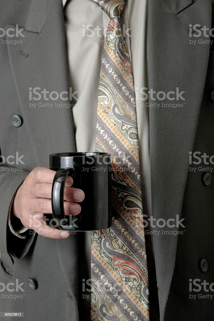 Man in business suit holding a cup of coffee royalty-free stock photo