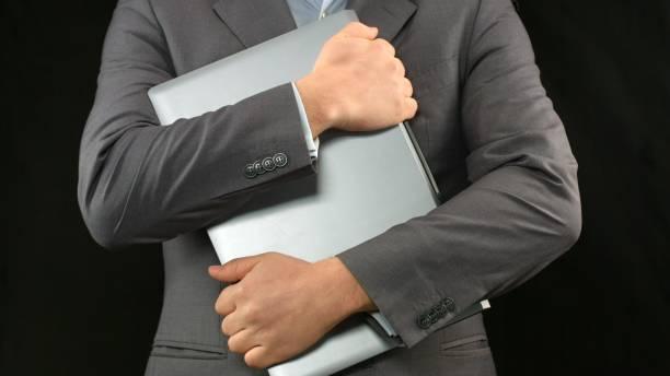 man in business suit holding laptop computer tight, personal data security - fare la guardia foto e immagini stock