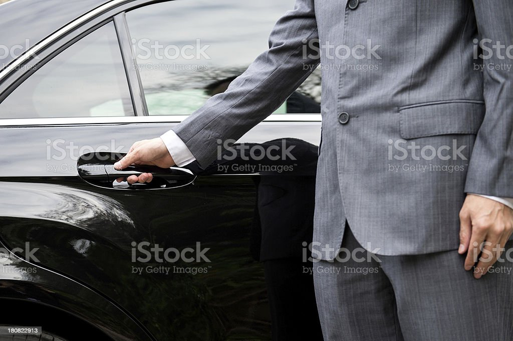 Man in business suit opening car door stock photo