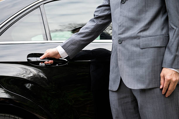 man in business suit opening car door - limousine service stock photos and pictures