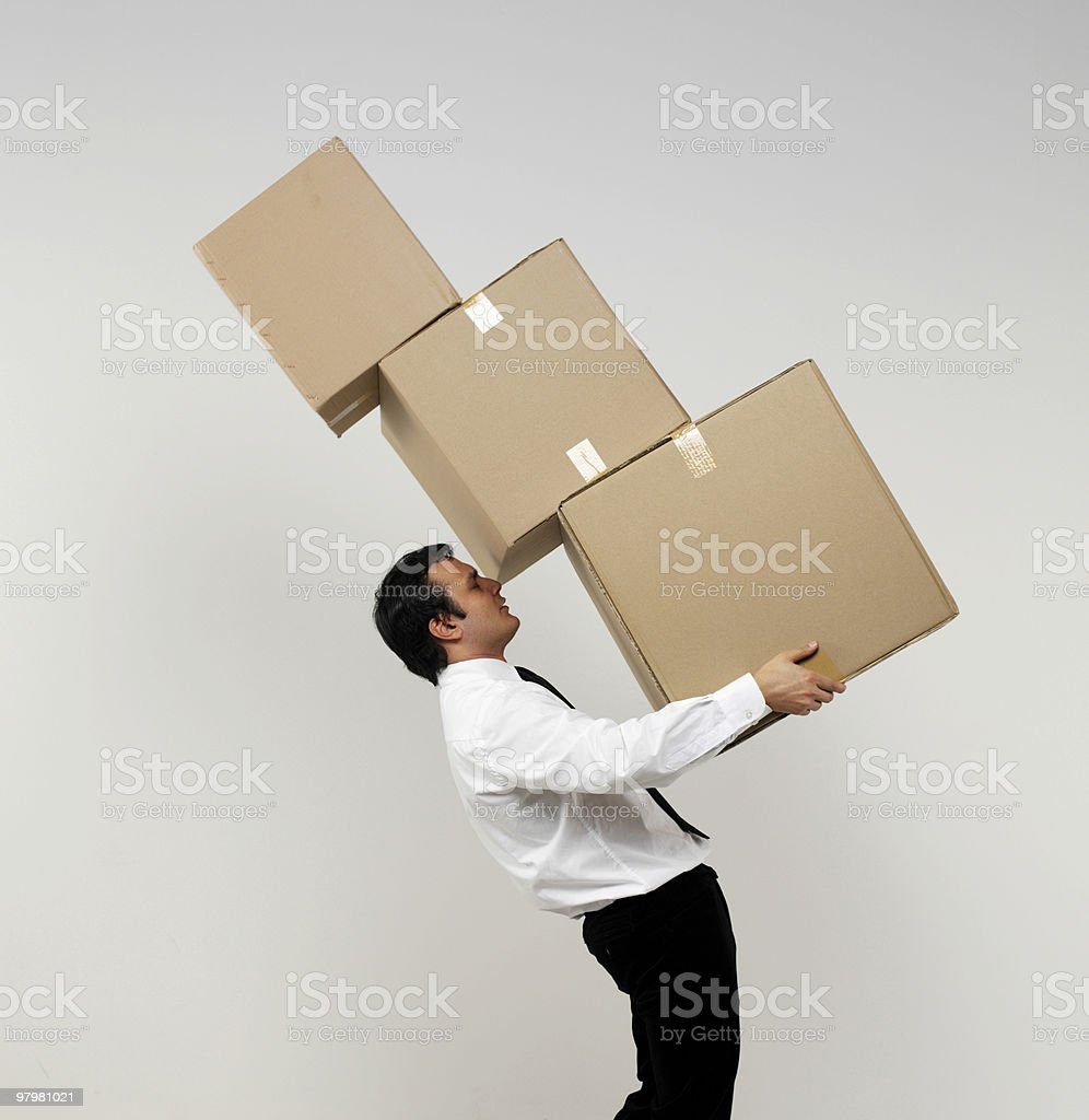 Man in business wear balancing three different sized boxes stock photo