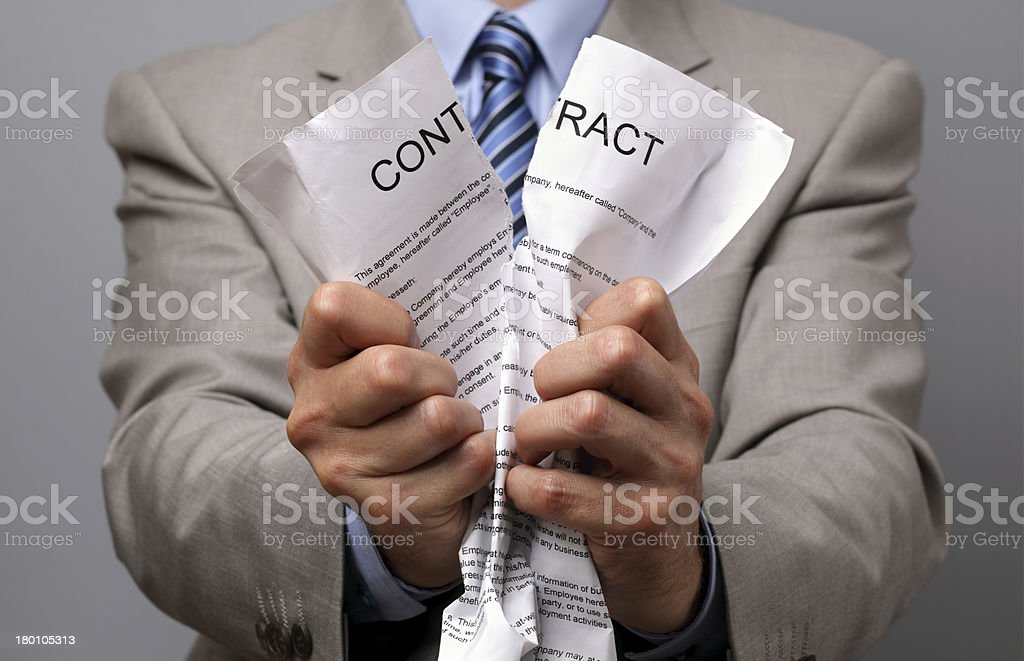 Man in business wear tearing up a contract with his hands stock photo