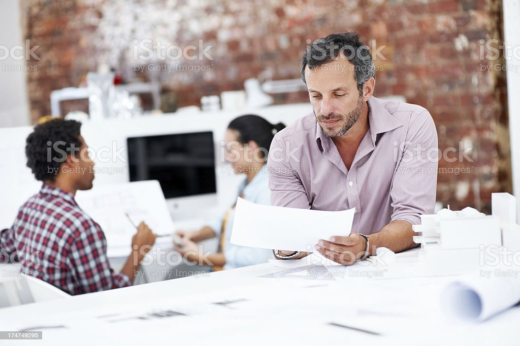 Man in button-down shirt looking at paperwork royalty-free stock photo
