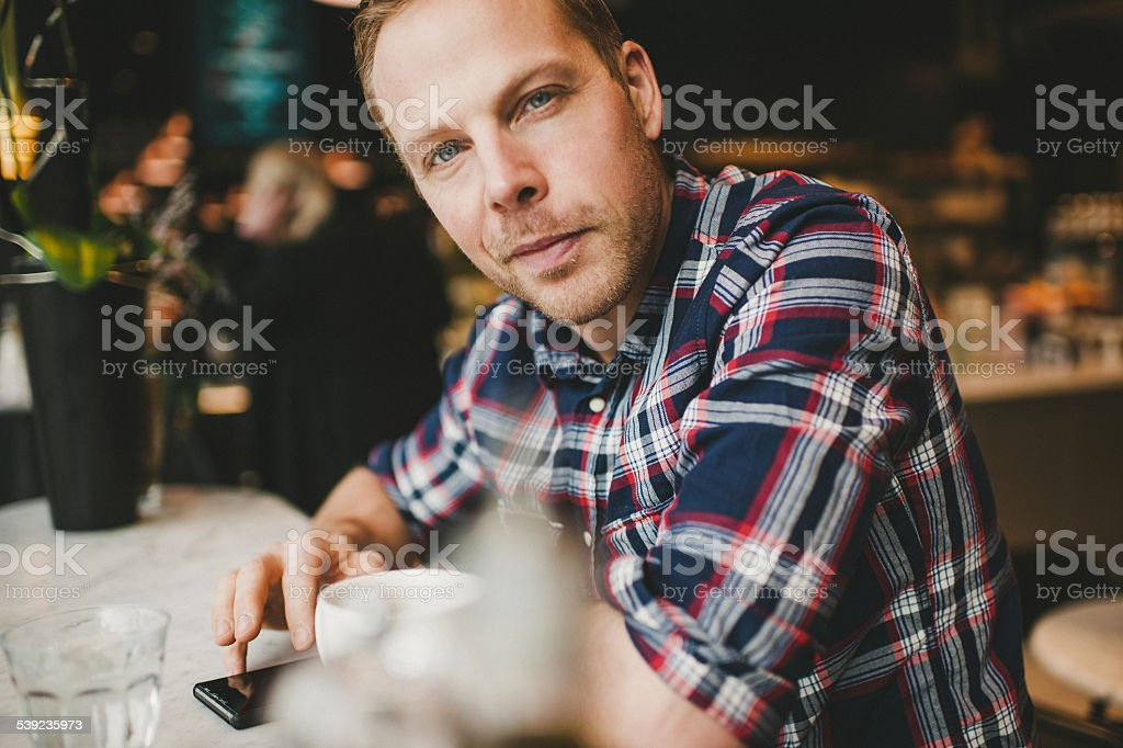 Man in cafe coffee shop playing with his smart phone royalty-free stock photo