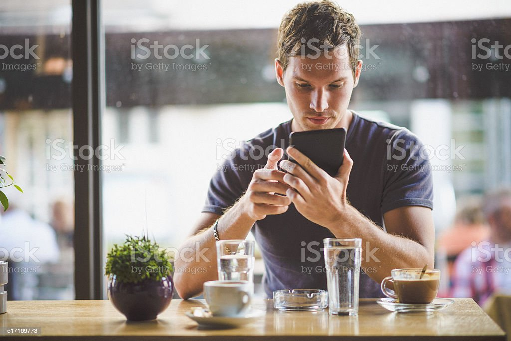 Man in cafe looking in tablet stock photo