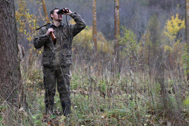 Man in camouflage and with guns in a forest belt on a spring hun A man in camouflage and with guns in a forest belt on a spring hunt poaching animal welfare stock pictures, royalty-free photos & images