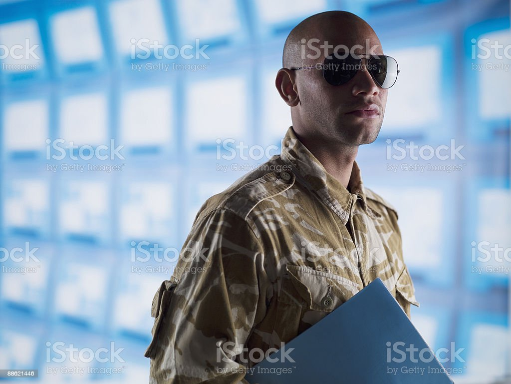 Man in camouflage holding folder near bank of computers royalty-free stock photo