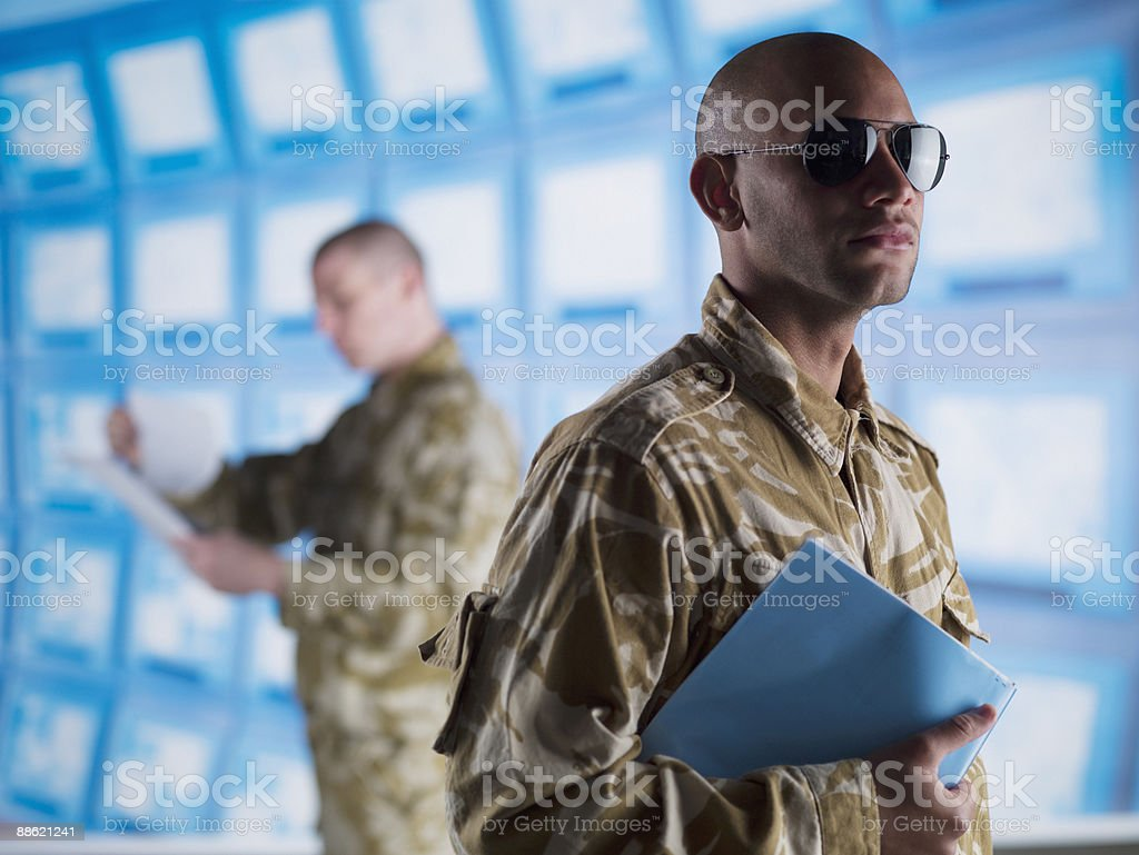 Man in camouflage holding folder stock photo