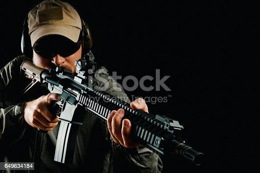 istock man in cap holding assault rifle 649634184