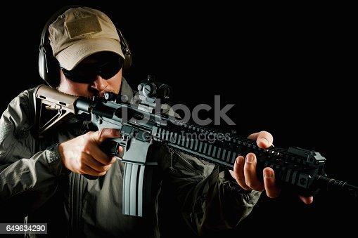 istock man in cap holding assault rifle 649634290
