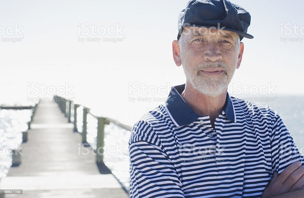 Man in cap standing on pier royalty-free stock photo