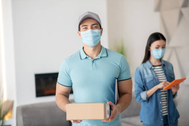 Mann in Kappe mit Box, Frau mit Tablette, in Schutzmasken. – Foto