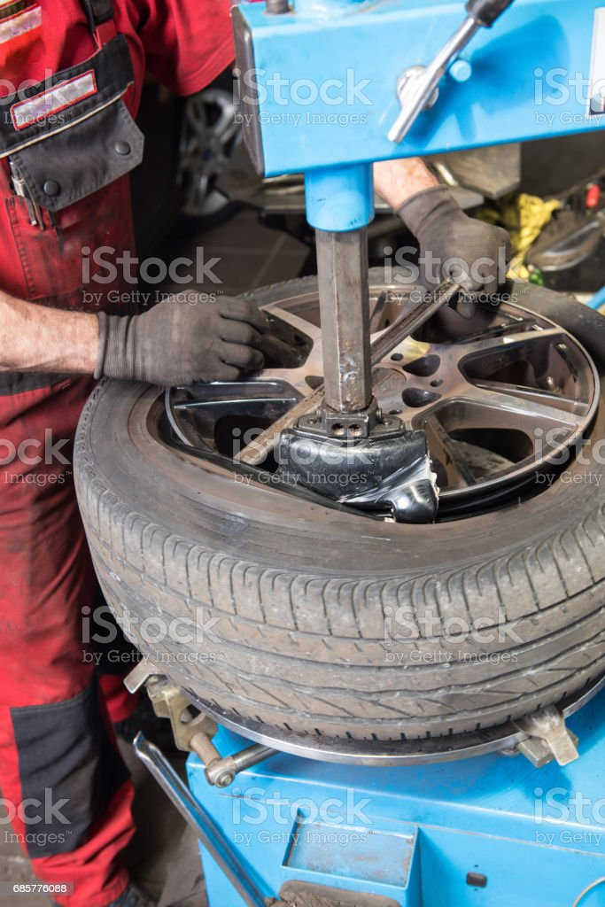 Man in Car repair levers a used tyre of the rim royalty-free stock photo