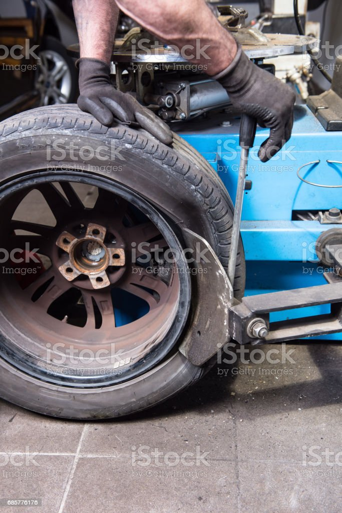 Man in Car repair levers a used tyre of the rim photo libre de droits