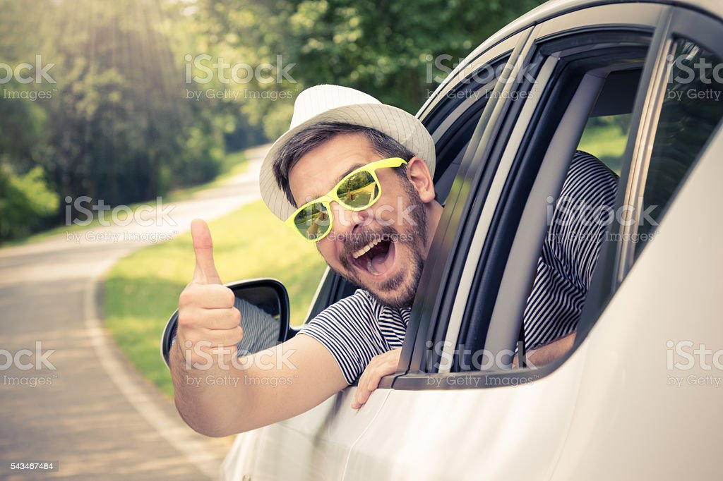 Man in car showing thumbs up stock photo