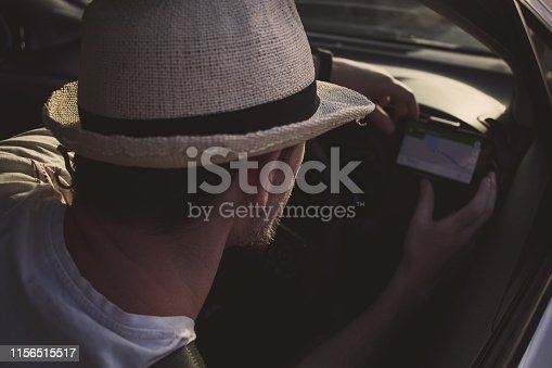 527894422istockphoto Man in car uses smartphone for navigation. Driving on vacation 1156515517