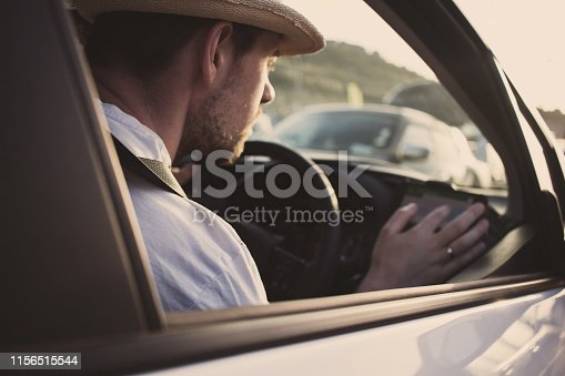 527894422istockphoto Man in car uses smartphone for navigation. Driving on vacation 1156515544