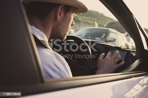 527894422istockphoto Man in car uses smartphone for navigation. Driving on vacation 1156515545