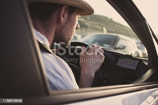 527894422istockphoto Man in car uses smartphone for navigation. Driving on vacation 1156515546