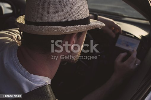 527894422istockphoto Man in car uses smartphone for navigation. Driving on vacation 1156515549